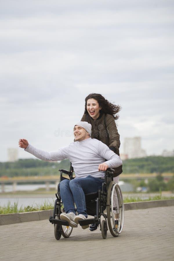 有年轻残疾人的快乐的妇女运行在码头的轮椅的 库存照片