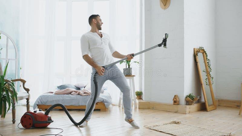 有年轻的人乐趣有吸尘器跳舞的清洁房子喜欢吉他弹奏者 免版税库存图片