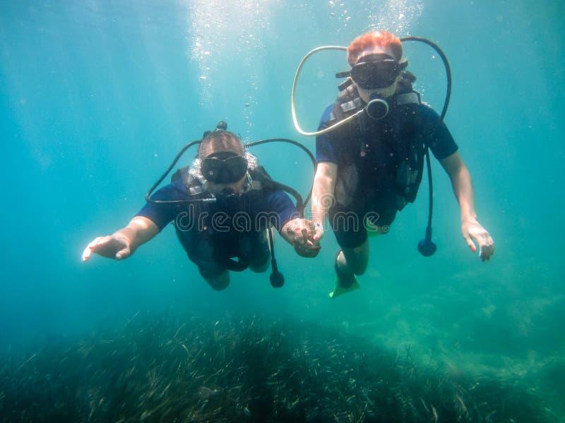 有年轻的夫妇佩戴水肺的潜水在水面下 免版税库存图片