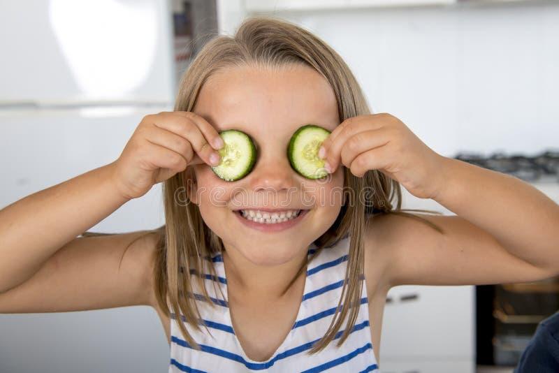 有年轻美好和可爱的女孩6或7的岁投入黄瓜切片的乐趣在家厨房在她眼睛微笑愉快 图库摄影