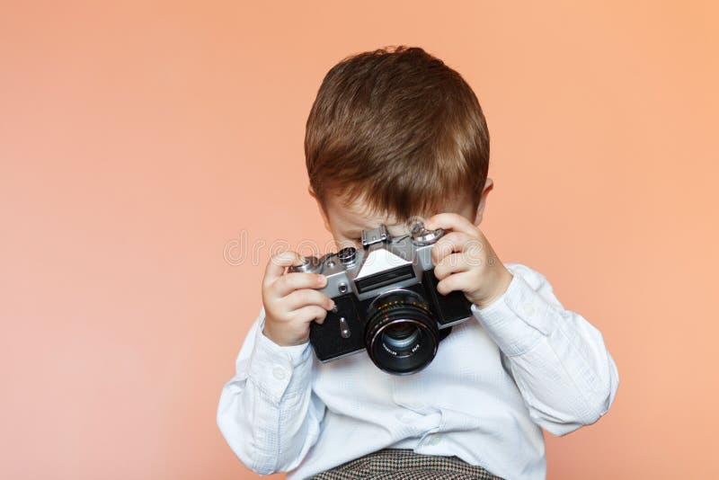 有年迈的减速火箭的照相机的小男孩 有一台老照相机的孩子 免版税图库摄影