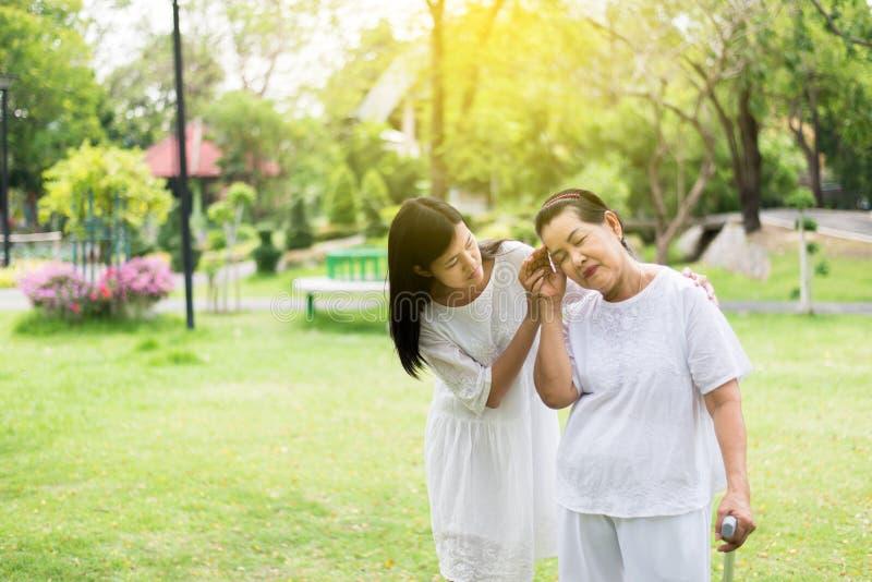 有年长亚裔的妇女从偏头痛疾病,女性的微弱的痛苦小心和支持 库存照片