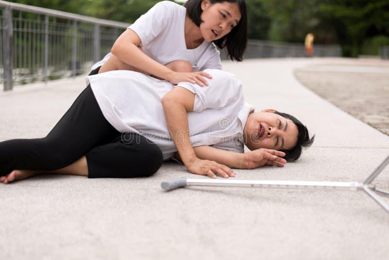 有年长亚裔的妇女从心脏攻击,女儿的胸口痛痛苦小心和支持 免版税库存照片