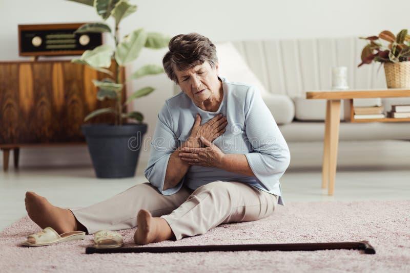 有年长的妇女心脏病发作 免版税库存照片