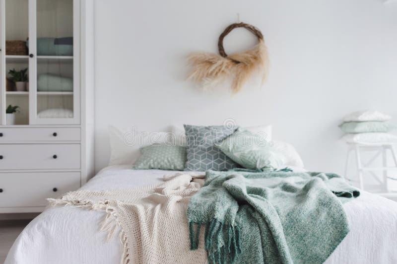 有床和枕头的现代斯堪的纳维亚晴朗的卧室 与白色墙壁和eco装饰的空间 一张床 免版税库存照片