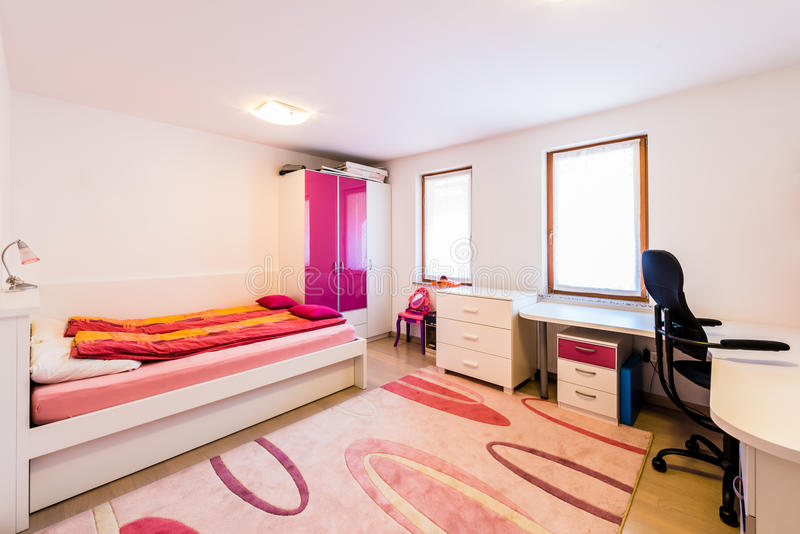 有床和研究书桌的现代儿童女孩戏剧室 库存照片