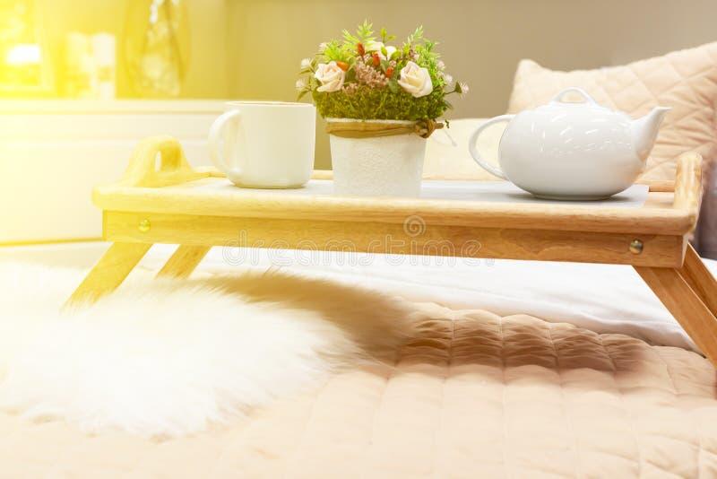 有床的卧室 在食物的床桌上 在落日 图库摄影