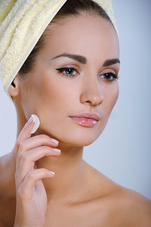 有应用化妆用品的理想的皮肤的美丽的女孩于她的表面 免版税库存图片
