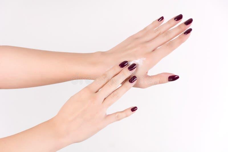 有应用在皮肤的红酒修指甲的柔和妇女手白色护手霜 免版税库存图片