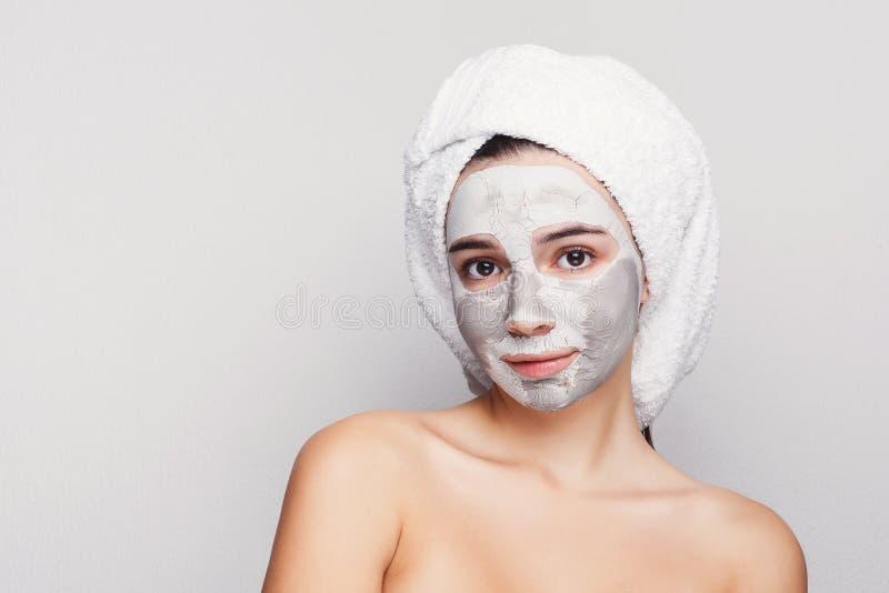 有应用的黏土面具的美丽的女孩在灰色背景 图库摄影