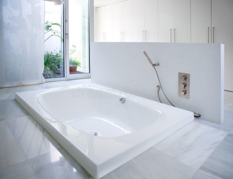 有庭院天窗的现代白色房子卫生间浴缸 图库摄影