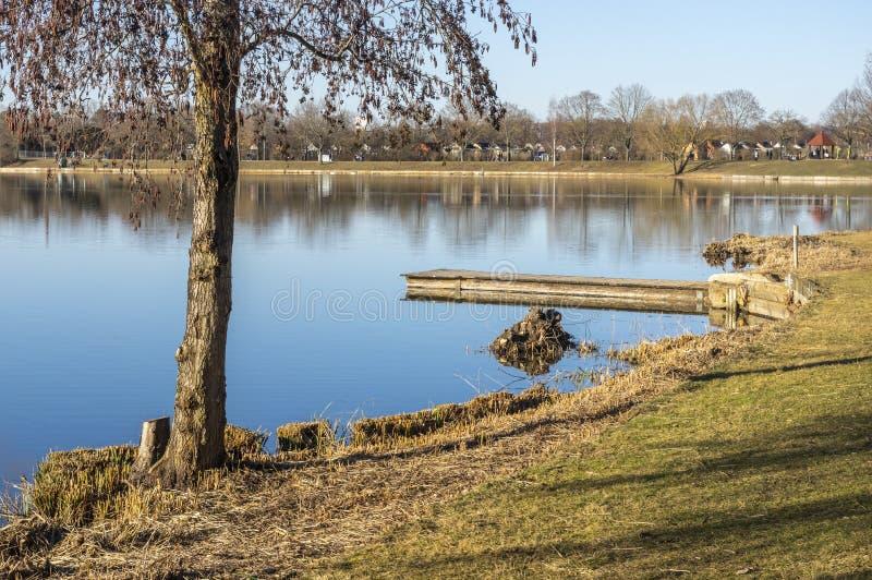 有康乐设施和消遣区域的田园诗湖在春天有毗邻的分配地段的 库存图片