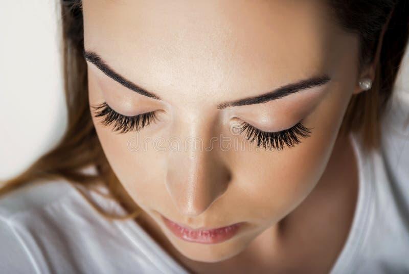 有延长的丝绸在美容院闭上的睫毛和眼睛的秀丽女孩,关闭  免版税库存照片