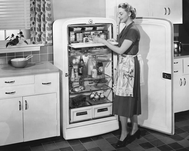 有开放冰箱的妇女(所有人被描述不更长生存,并且庄园不存在 供应商保单那里wil 免版税库存图片