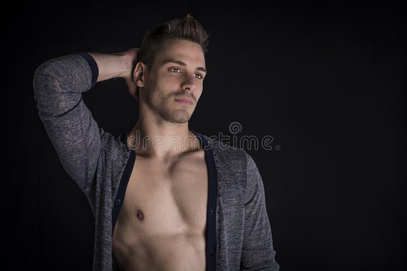 有开放毛线衣的英俊的年轻人在赤裸胸口。 库存照片