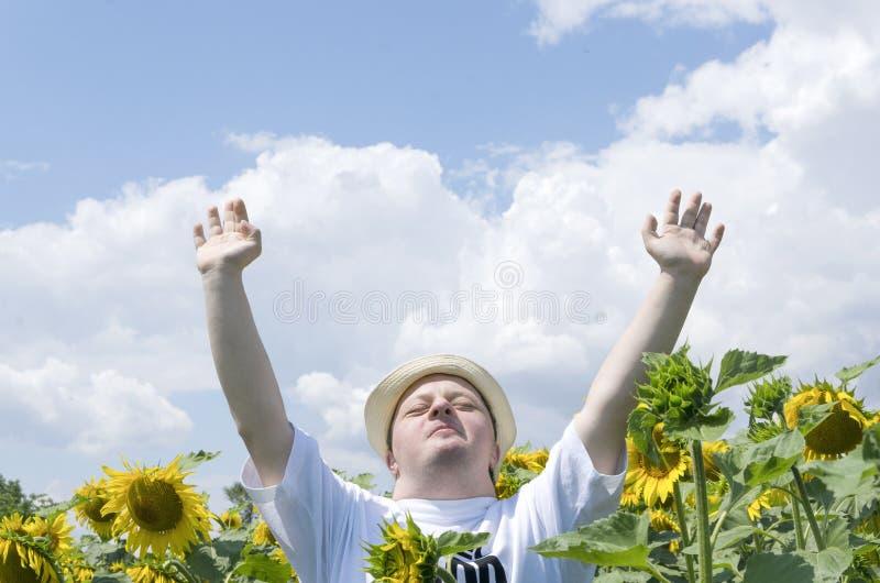 有开放胳膊的愉快和感恩的年轻人在向日葵领域 库存照片