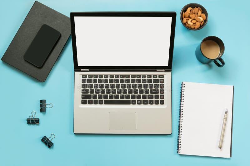 有开放膝上型计算机的,在办公室蓝色桌上的辅助部件工作场所 顶视图和拷贝空间 图库摄影
