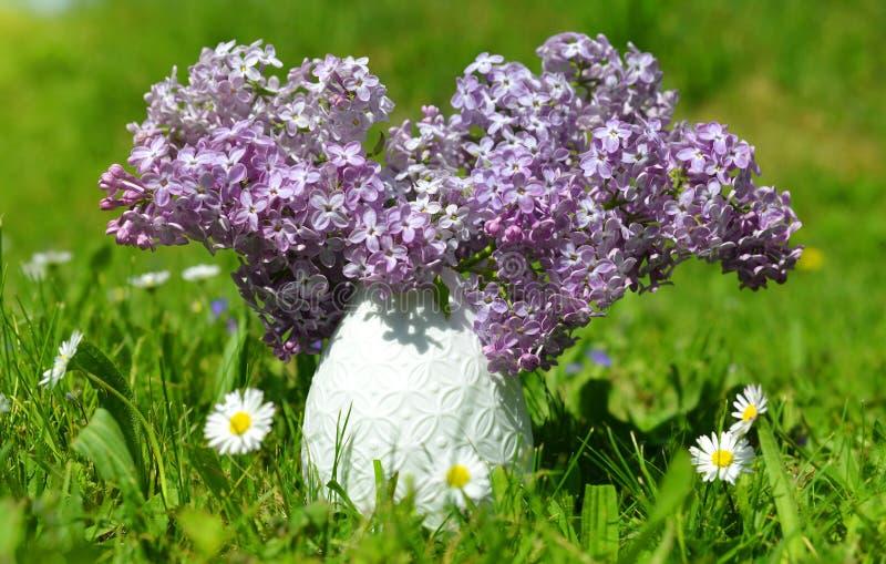 有开花的紫色淡紫色花的花瓶 免版税库存图片