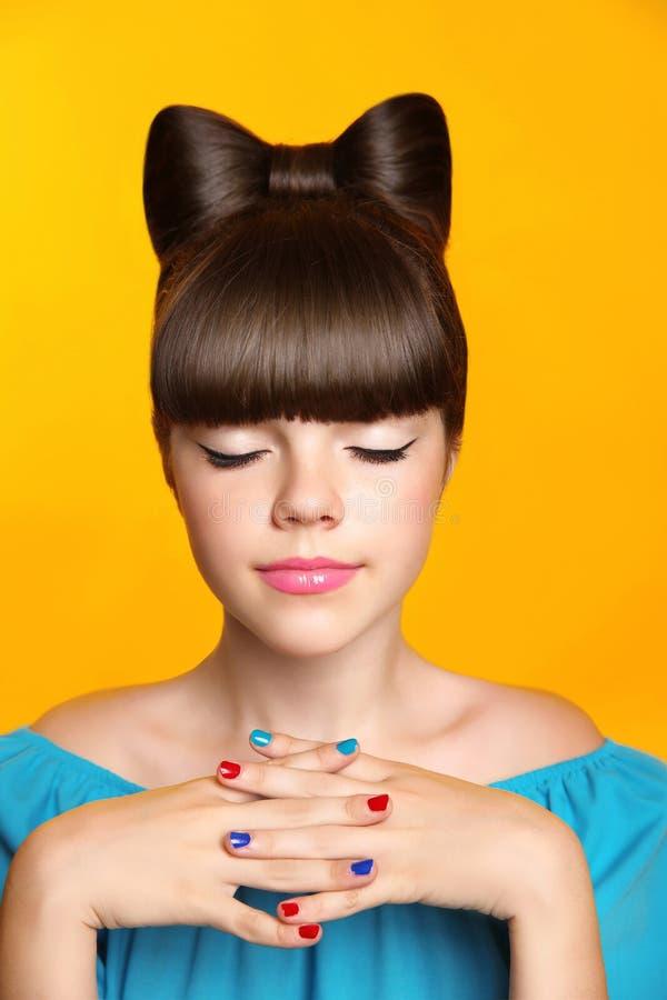 有弓发型,构成和colou的美丽的微笑的青少年的女孩. 乐趣, 头发.图片