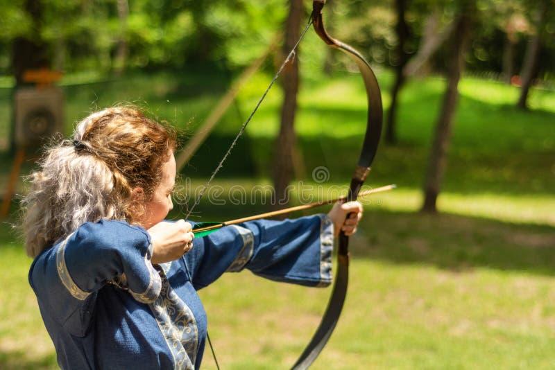 有弓射击箭头的妇女射手在骑士节日的森林里在一套传统衣服 图库摄影