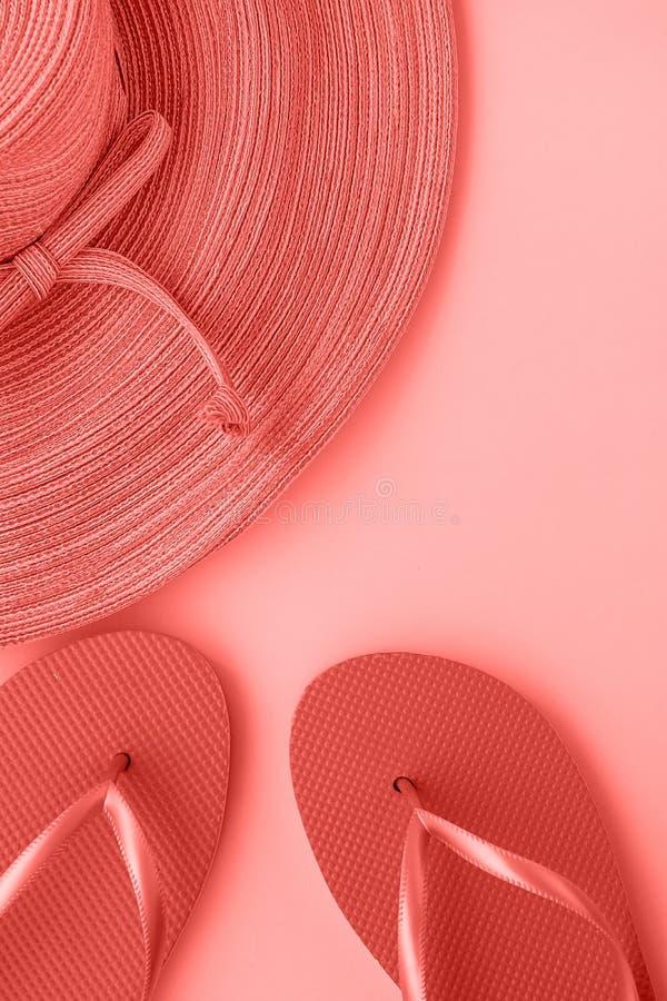 有弓拖鞋的端庄的妇女草帽在单色桃红色背景的时髦生存珊瑚颜色 海滩假期时尚 库存照片