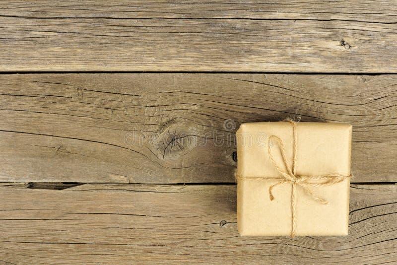 有弓的布朗包装纸礼物盒在土气木头 库存图片