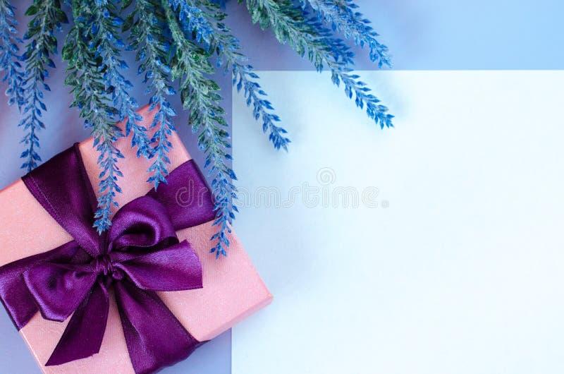 有弓的桃红色在紫罗兰色背景白色空白的礼物盒和淡紫色 库存照片