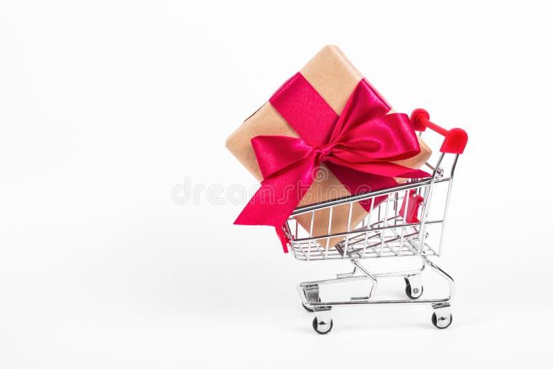 有弓的礼物盒在购物台车 有大礼物盒的购物车在白色背景 库存图片