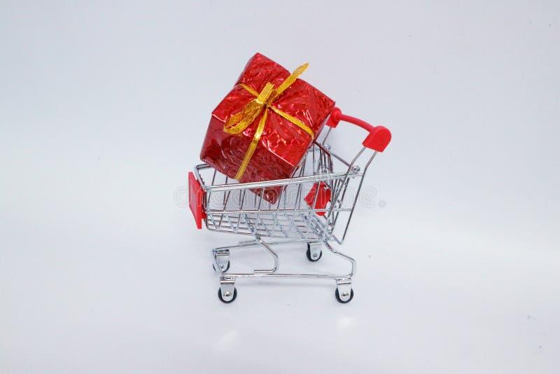 有弓的红色礼物盒在手推车圣诞节概念,在白色背景隔绝 免版税库存图片