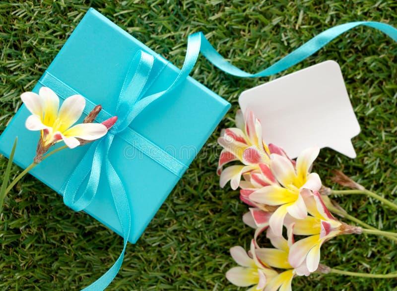 有弓的蓝色礼物盒,文本的空白的笔记和花 图库摄影