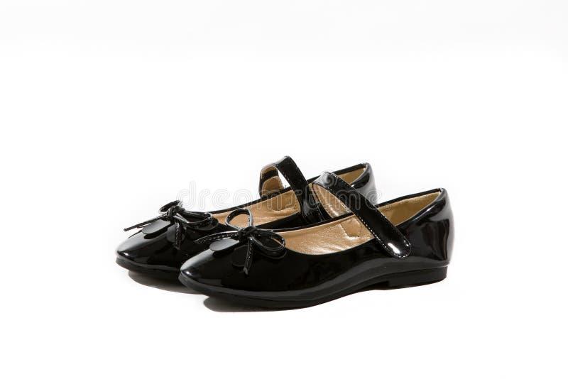 有弓的黑漆革女孩玛丽珍鞋子 免版税图库摄影