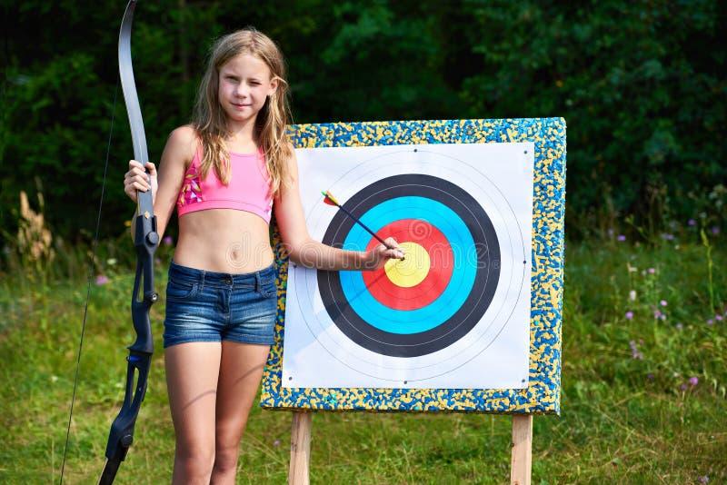 有弓箭的女孩少年在目标附近 库存照片