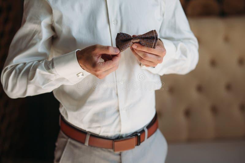有弓领带的新郎手 典雅的绅士clother、白色衬衣和棕色传送带 免版税库存图片