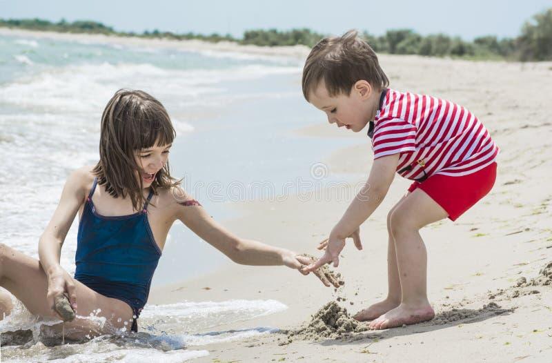 有弟弟的更老的姐妹被修造在海滨的沙子, 库存图片