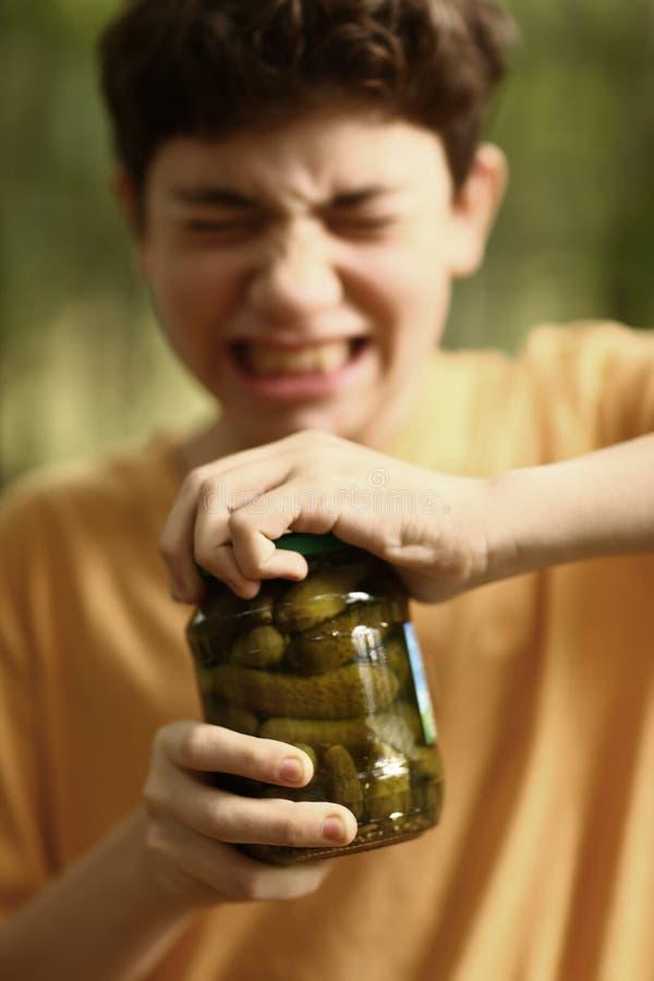 有张力去除盖子的鬼脸尝试的男孩从黄瓜刺激 免版税库存图片