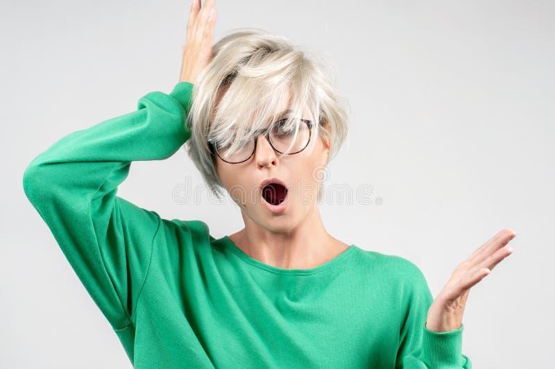 有张的嘴的震惊妇女在灰色背景的玻璃 免版税库存照片