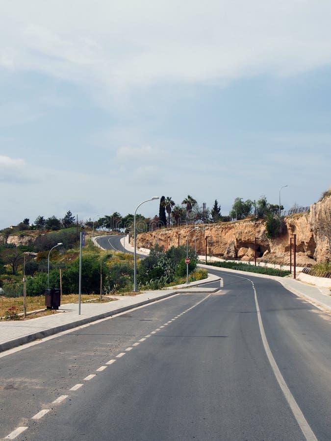 有弯曲小山的路面和路灯柱的空的双线路入与周围的树和蓝色被日光照射了天空的距离 图库摄影