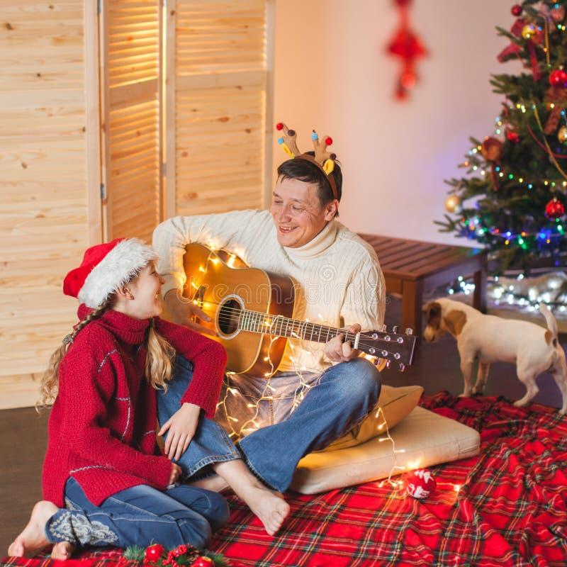 有弹吉他和唱歌在圣诞节tr附近的爸爸的女孩 库存照片