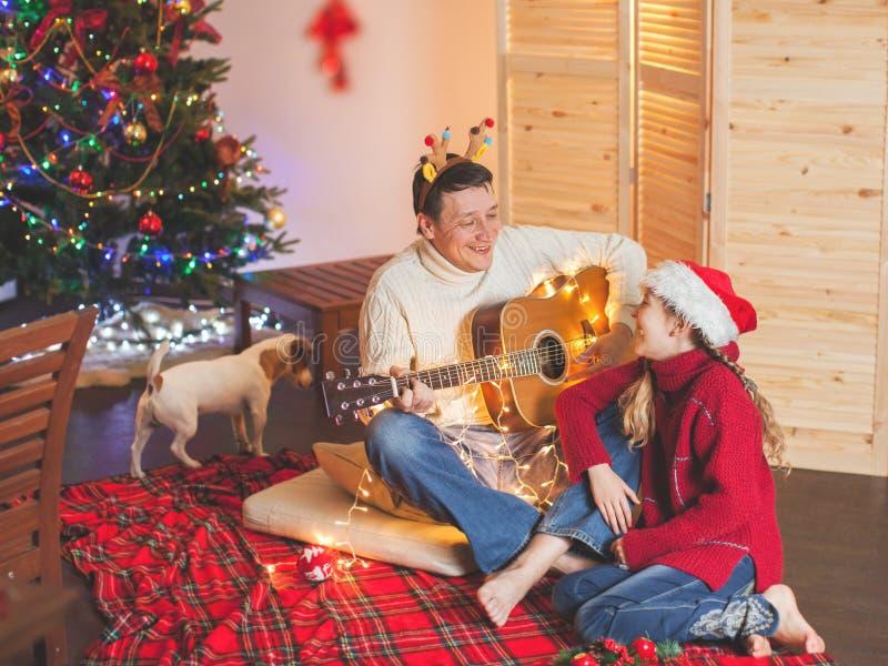 有弹吉他和唱歌在圣诞节tr附近的爸爸的女孩 库存图片