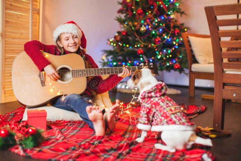 有弹吉他和唱歌在圣诞节tr附近的狗的女孩 库存图片