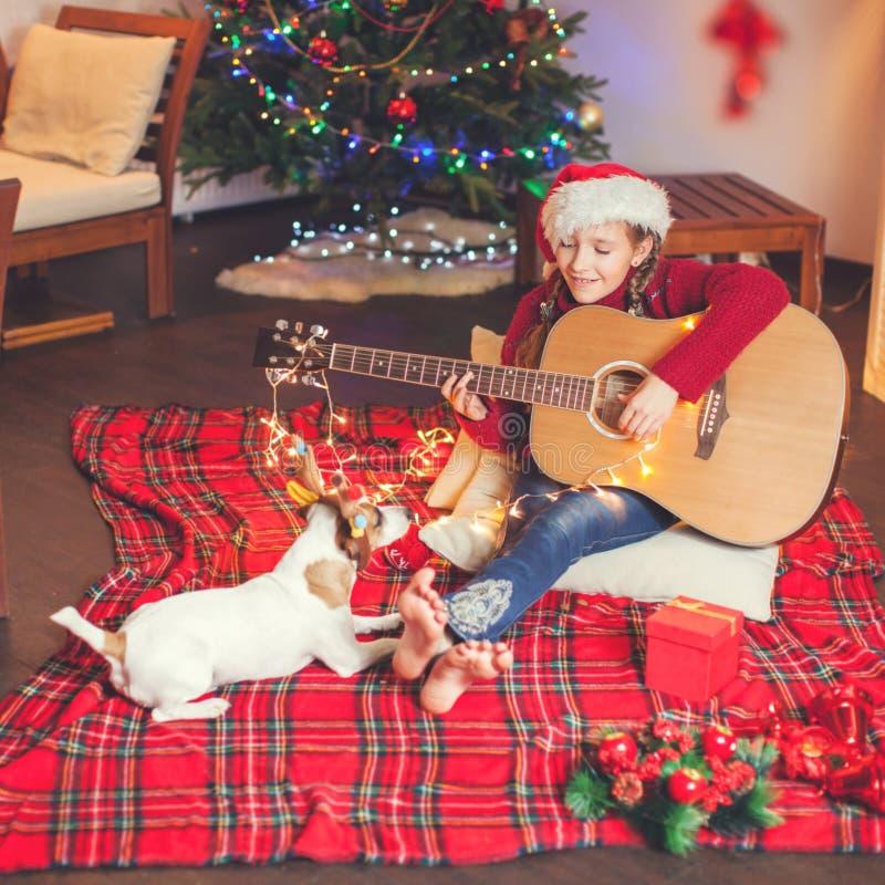 有弹吉他和唱歌在圣诞节tr附近的狗的女孩 免版税库存图片