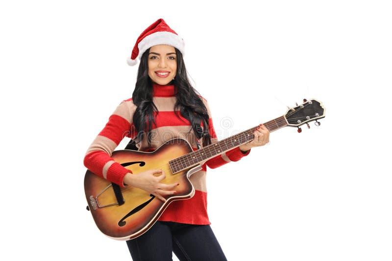 有弹吉他的圣诞老人帽子的少妇 免版税库存图片