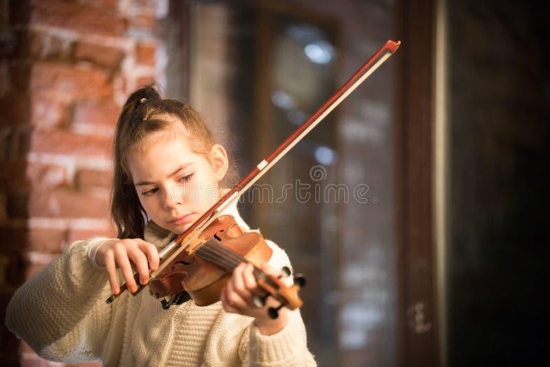 有弹小提琴的长发的一小美女 免版税库存图片