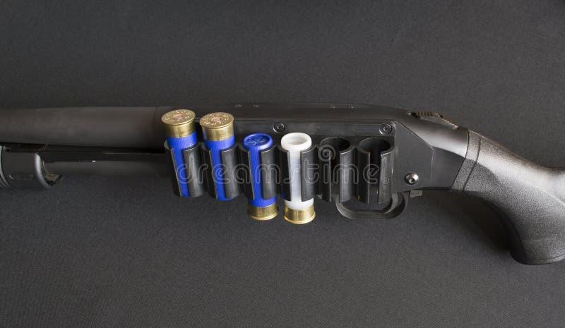 有弹药筒的泵浦步枪在子弹带 免版税库存图片