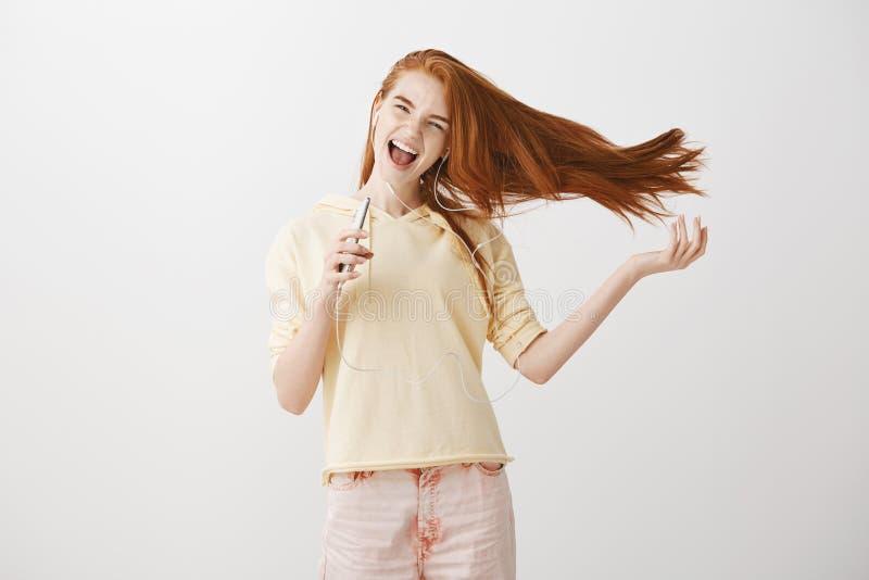 有强有力的声音的感情妇女兴奋了对与耳机的巨大声音的goosebumps 快乐的有吸引力的红头发人 免版税图库摄影