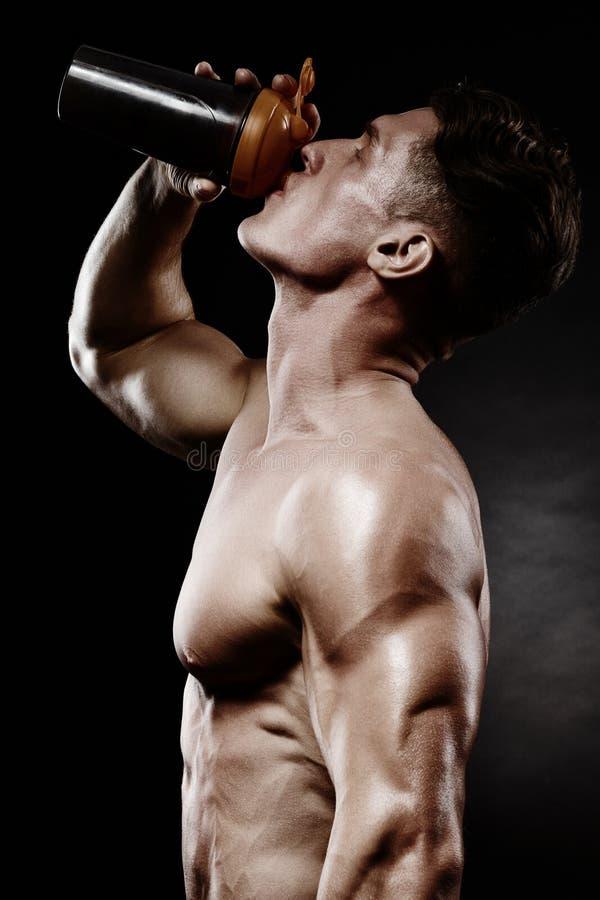 有强的肌肉的年轻英俊的人,在trai以后的蛋白质饮料 库存照片