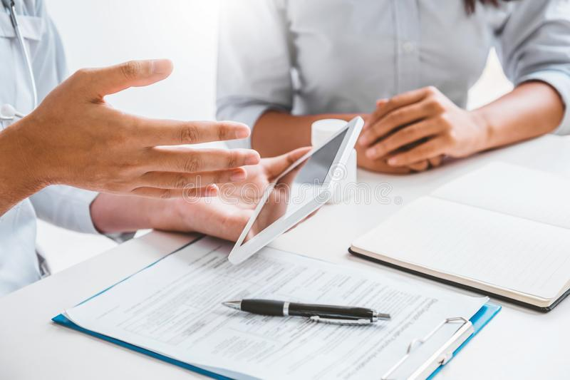 有当前关于在数字片剂的治疗指南的患者的医生在办公室 免版税图库摄影