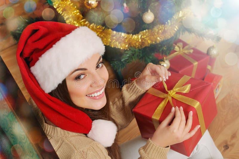 有当前箱子的微笑的少妇在圣诞节t的圣诞老人帽子 免版税库存照片