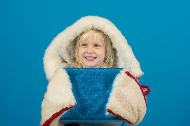 有当前组装的儿童女孩或在网络星期一的礼物盒 蓝色背景的孩子 图库摄影