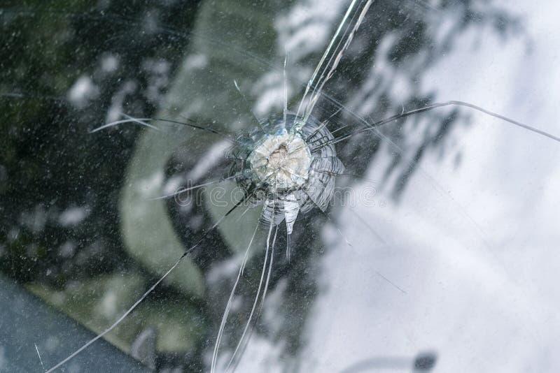 有径向裂纹和一个孔的残破的汽车挡风玻璃在中部 免版税库存照片